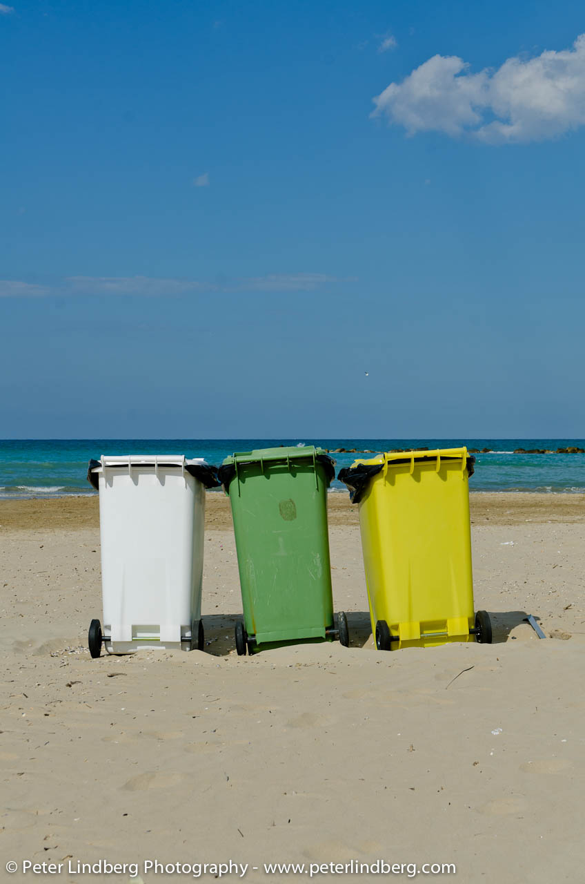 Three garbage-cans on the beach in Roseto. Waste, recycling and paper